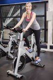 Fit woman on exercise bike. At the gym Stock Image