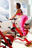 Fit woman on exercise bike at the gym Stock Image