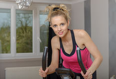Fit woman on exercise bike  at home. Fit blonde woman on exercise bike at home Stock Photos