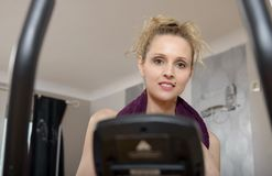 Fit woman on exercise bike  at home. Fit blonde woman on exercise bike at home Royalty Free Stock Image