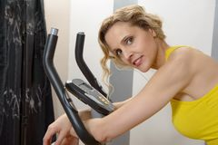 Fit woman on exercise bike  at home. Fit blonde woman on exercise bike at home Stock Photo