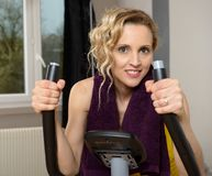 Fit woman on exercise bike  at home. Fit blonde woman on exercise bike at home Stock Image