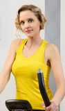 Fit woman on exercise bike  at home. Fit blonde woman on exercise bike at home Royalty Free Stock Photos