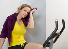 Fit woman on exercise bike  at home. Fit blonde woman on exercise bike at home Royalty Free Stock Photography