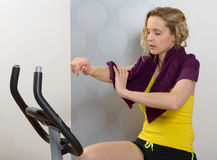 Fit woman on exercise bike  at home. Fit blonde woman on exercise bike at home Stock Photography