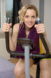 Fit woman on exercise bike  at home. Fit blonde woman on exercise bike at home Royalty Free Stock Photo