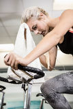 Fit woman on exercise bike wiping sweat with towel Stock Photos