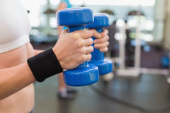 Fit woman exercising with blue dumbbells Royalty Free Stock Photos