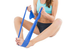 Fit woman exercising with a blue yoga belt Royalty Free Stock Images