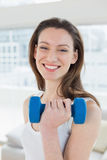 Fit woman exercising with dumbbell in fitness studio Stock Photography