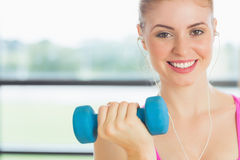 Fit woman exercising with dumbbells in fitness studio Stock Photography