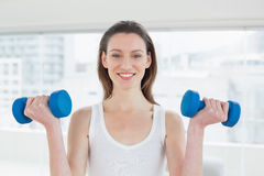 Fit woman exercising with dumbbells in fitness studio Royalty Free Stock Photography