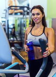 Fit woman exercising at fitness gym aerobics elliptical walker trainer workout. Royalty Free Stock Images