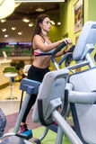 Fit woman exercising at fitness gym aerobics elliptical walker trainer workout. Stock Photo