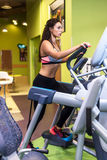 Fit woman exercising at fitness gym aerobics elliptical walker trainer workout. Stock Photos