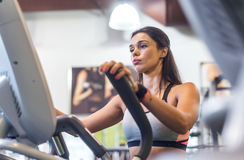 Fit woman exercising at fitness gym aerobics elliptical walker trainer workout. Royalty Free Stock Photography