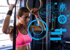 Fit woman exercising in gym with futuristic interface. Digital generated image of fit woman exercising in gym with futuristic interface Royalty Free Stock Image