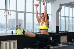 Fit woman exercising with gymnastic rings raising legs in gym. Fit woman exercising with gymnastic rings raising legs in gym royalty free stock photo