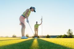 Fit woman exercising hitting technique during golf class with an Royalty Free Stock Photography