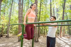 Fit woman exercising on parallel bar with her boyfriend Stock Photos