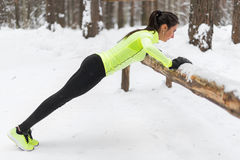 Fit woman exercising in woods doing push ups on a log at park. Outdoor training workout winter morning side view. stock photo