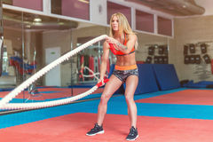 Fit woman Fitness battling ropes at gym workout. royalty free stock images