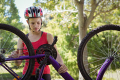 Fit woman fixing the chain on her bike Royalty Free Stock Images