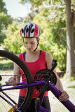 Fit woman fixing the chain on her bike Royalty Free Stock Photography