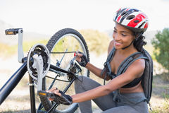 Fit woman fixing the chain on her bike Royalty Free Stock Image