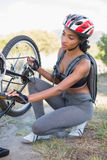 Fit woman fixing the chain on her bike Stock Photo