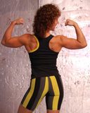 Fit woman flexing her back and arms. Female in sports attire flexing her back she's in stripped spandex and smileing Stock Photography