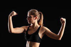 Fit woman flexing muscles during exercise workout. Sexy young woman wearing black sports bra, with fit, toned body. Woman has both arms raised, fists clenched Stock Image