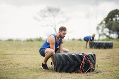 Fit woman flipping a tire during obstacle course stock photo