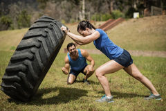 Fit woman flipping a tire while trainer cheering during obstacle course. Fit women flipping a tire while trainer cheering during obstacle course in boot camp Royalty Free Stock Images