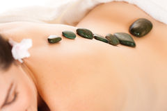 Fit woman getting a hot stone massage. Fit young woman getting a relaxing hot stone massage Stock Photo