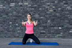 Fit woman giving double thumb up. Fit woman in pink top and black tights giving double thumb up near grey brick wall Stock Photos