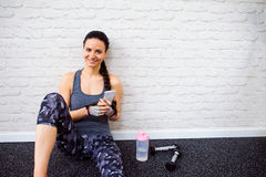 Fit woman in gym holding smart phone, brick wall Royalty Free Stock Photos