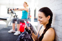 Fit woman in gym holding smart phone, brick wall. Smiling attractive fit women in gym sitting on a floor holding smart phone against white brick wall Royalty Free Stock Image