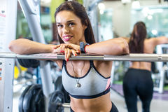 Fit woman in a gym looking at camera, resting after exercise with barbell. Royalty Free Stock Images