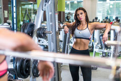 Fit woman in a gym looking at camera, resting after exercise with barbell. Royalty Free Stock Image