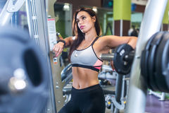 Fit woman in a gym looking at mirror, resting after exercise with barbell. Royalty Free Stock Photography