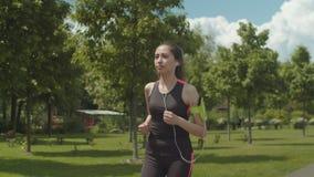 Fit woman in headphones running on park lane stock video footage