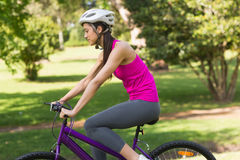Fit woman with helmet riding bicycle at park Royalty Free Stock Photo