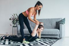 Fit woman helping friend in back stretching workout at home. Fit women helping friend in back stretching workout at home Stock Photos