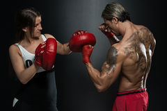 Fit Woman And Her Trainer Boxing Indoors Royalty Free Stock Photography