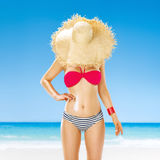 Fit woman hide behind straw hat on seashore applying sun cream. Perfect summer. fit woman hide behind straw hat on the seashore applying sun cream Royalty Free Stock Photo