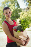 Fit woman holding bag of healthy groceries Royalty Free Stock Images