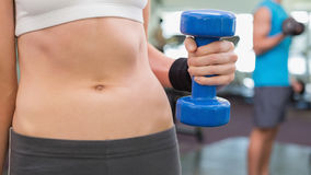 Fit woman holding blue dumbbell mid section Stock Photography