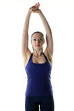 Fit woman holding both her hand up in the air to stretch. Image of a fitness model doing a shoulder and lat stretch Royalty Free Stock Photos