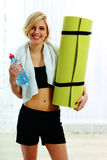 Fit woman holding a bottle with water and yoga mat Royalty Free Stock Photo